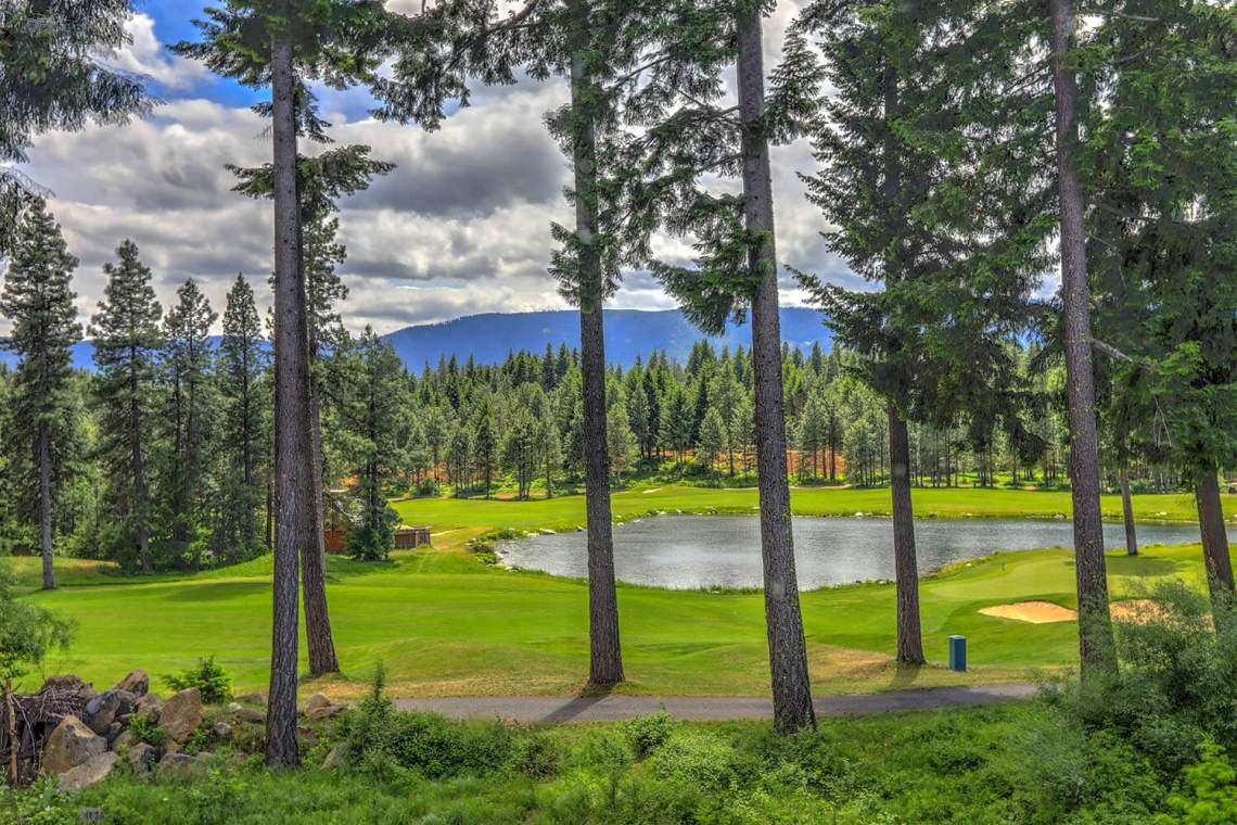 Golf course with pine trees and pond in cascade mountains of Northwest with little house.